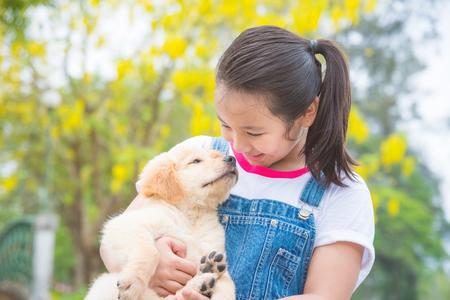 Young asian girl holding a little golden retriever dog in park