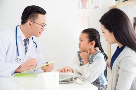Young asian girl with sore throat come to visit doctor with her mother at clinic