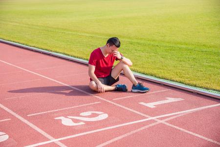 Trauriger asiatischer Mann, der auf dem Boden sitzt und weint, nachdem er im Wettbewerb verloren hat