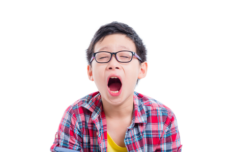 Young asian boy yawning over white
