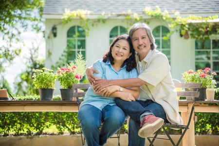 Gepensioneerd echtpaar zit voor hun huis en glimlacht gelukkig