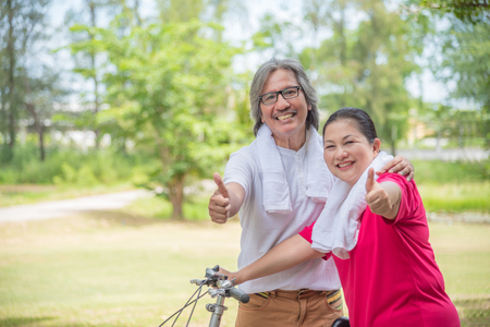 Happy asian retired couple showing thumb up and smile in park