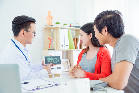 Der asiatische Arzt erklärt dem asiatischen Paar im Krankenhaus das Ultraschallergebnis Standard-Bild