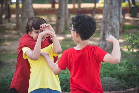 Young asian boy bullied by two boys in park