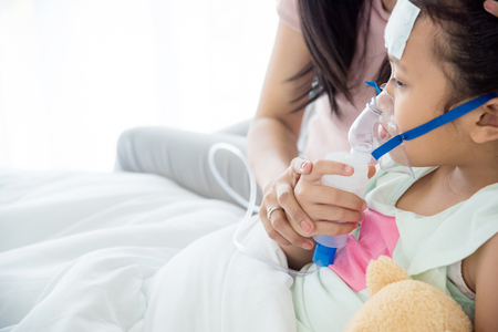 Young asian sick girl sitting on bed with oxygen mask