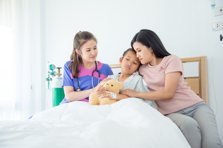 Young asian female doctors visiting child patient on ward Stock Photo