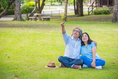 Senior Asian Couple Relaxing In Park Together