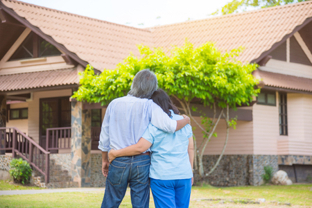 Asian senior couple from behind looking at front of house