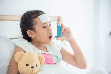 Young asian girl sitting on bed and using broncodilator inhaler for relieve asthma symptom Stock Photo