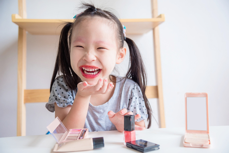 Little asian girl laughing after make up face by herself
