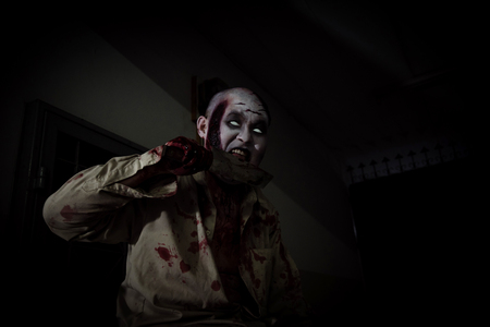 Male zombie holding and licking blood on knife in dark room Stock Photo