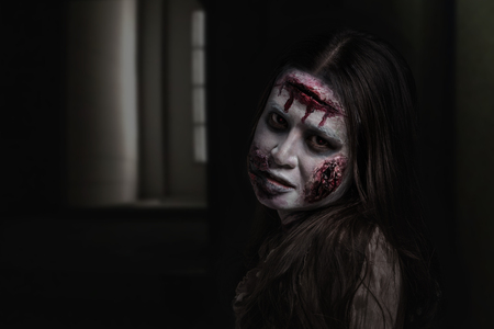 Asian female zombie standing in dark room and looking at camera