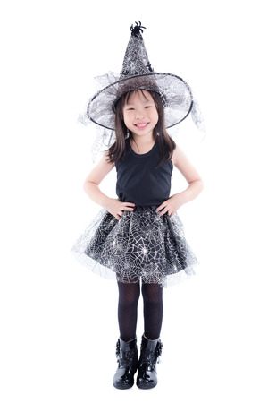 Full length of little asian girl wearing witch costume for Halloween standing isolated over white background