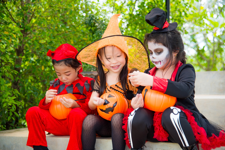 Little asian girls in Halloween costume sitting on stair and smile