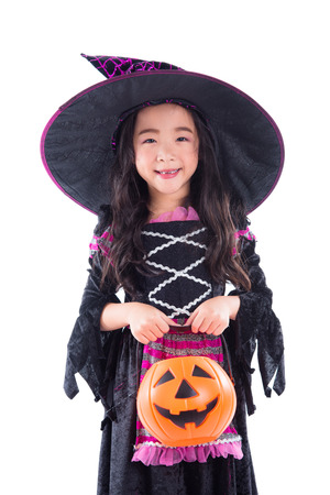 Little asian girl witch with holding pumpkin bucket and smiles over white background