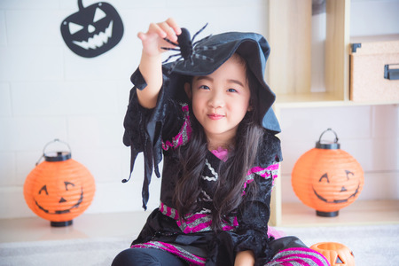 Little asian girl in witch costume sitting in room decorated for Halloween day Stock Photo