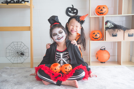 Little asian girls sitting and smile in room decorated for Halloween day