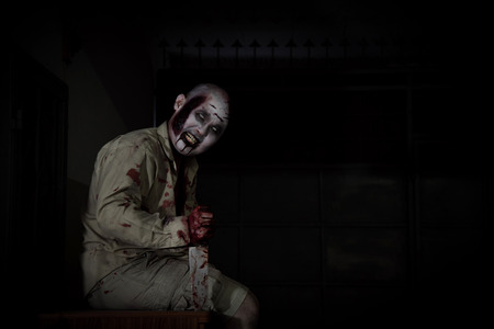 Male zombie sitting and smiles in dark room Stock Photo