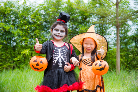 Little asian girls in Halloween costume standing in park and smile