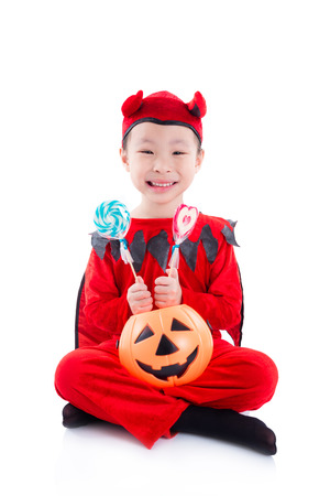 Little asian girl in devil halloween costume sitting over white background Stock Photo