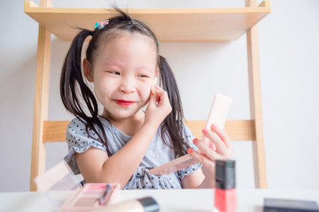 Little asian girl make up her face and smile happily while looking in mirror