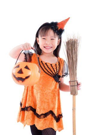 Little girl wearing witch Halloween costume standing with broom over white background Stock Photo