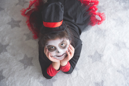 Little asian girl in Halloween costume lying on the floor and looking at camera