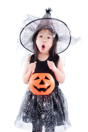 little asian girl wearing witch costume for Halloween holding pumpkin bucket isolated over white background