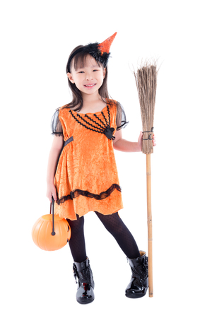 Full length of Little girl wearing witch Halloween costume standing with broom over white background