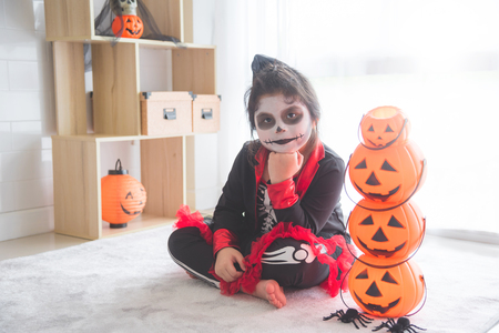 Little asian girl sitting and smile in room decorated for Halloween day Stock Photo