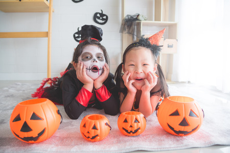 Little asian girls lying and smile in room decorated for Halloween day