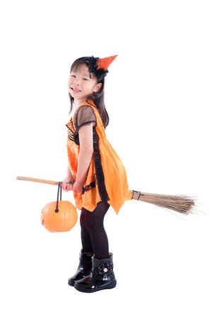 Full length of Little girl wearing Halloween costume riding broom over white background