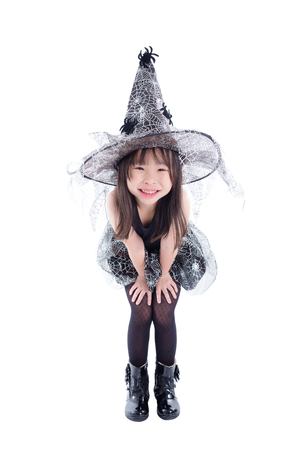 Full length of little asian girl wearing witch costume for Halloween isolated over white background