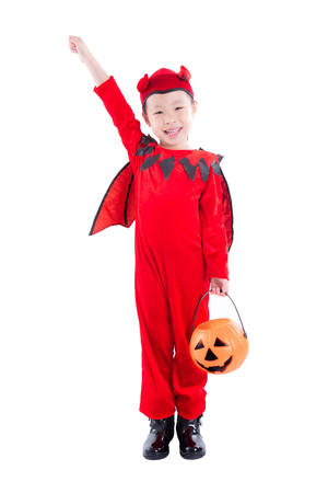 Little asian girl in devil halloween costume standing over white background