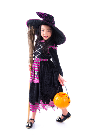 Full length of little asian girl witch with a broom standing over white background
