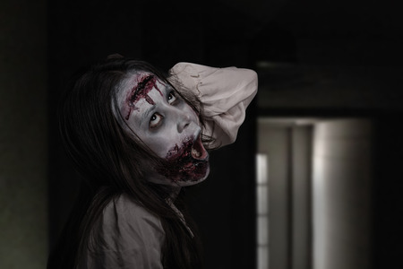 Asian female zombie standing and screaming in dark room Stock Photo