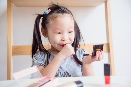 Little asian girl applying red color lipstick on her lips