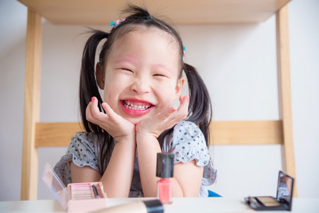 Little asian girl smiling happily after make up face by herself