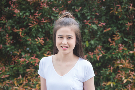 Beautiful asian woman smiling in front of leave wall in garden