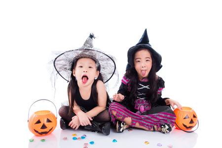 Asian children wearing halloween costume sitting on the floor over white background