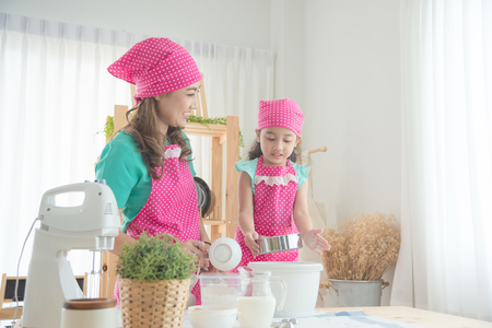 Beautiful asian mother and daughter wearing pink apron making cake in the kitchen. Stock Photo