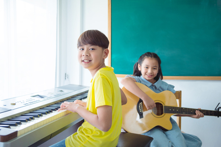 Happy Asian kids playing Music Instruments and smile In School classroom