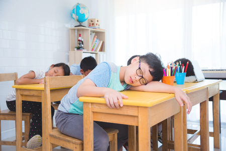 Tired asian elementary school student falling asleep while studying in classroom