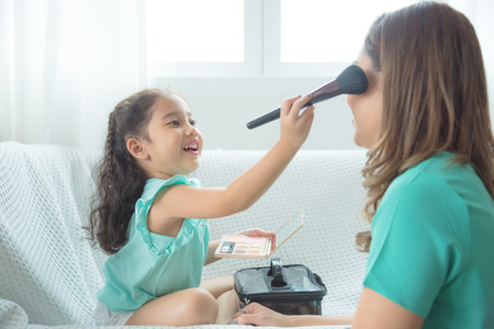 Cute asian daughter putting makeup on her mother face at home.