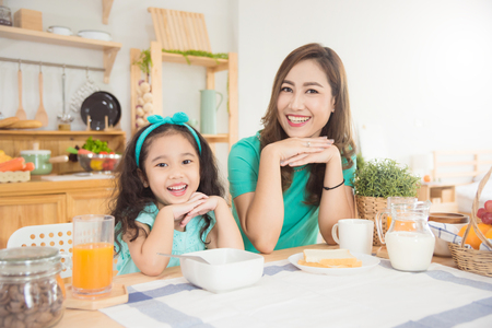 Beautiful asian mother and daughter having breakfast together at home in the morning Standard-Bild - 111402406