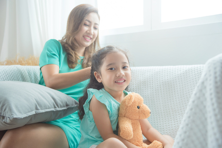 Asian mother Braiding hair To her daughter Before going to school