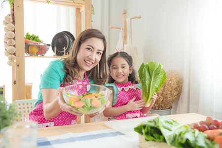 Beautiful asian mother and daughter wearing pink apron cooking breakfast in the kitchen.