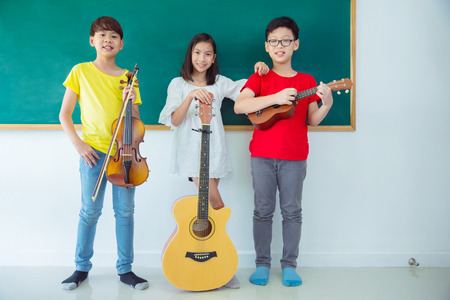 Group of happy Asian kids with Music Instruments standing and smile In School classroom Stock Photo