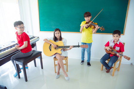 Group of happy Asian kids playing Music Instruments and smile In School classroom Stock Photo