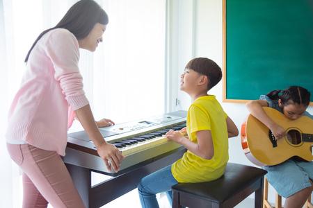 Beautiful asian female teacher teaching kids playing Music Instruments In School classroom